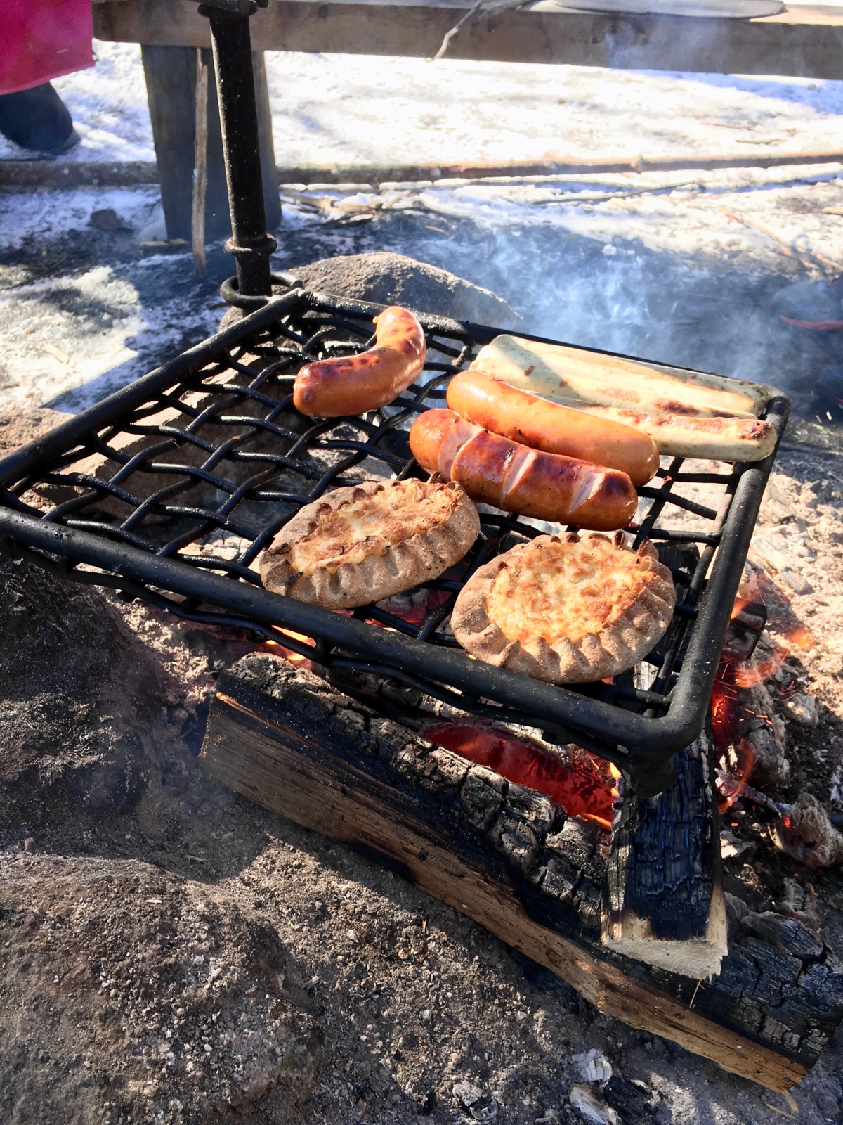 Makkaran ja karjalanpiirakan paistoa  nuotiolla Nuuksiossa maaliskuussa 2018.