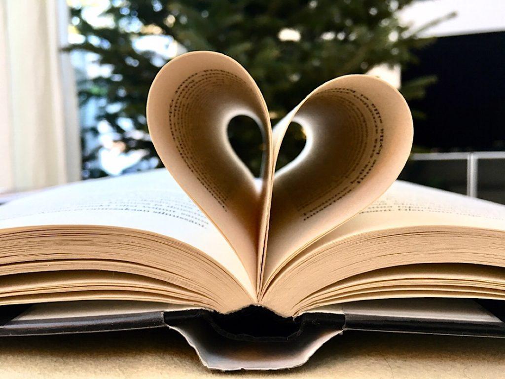 Kirja kuvattuna sivusta siten, että keskiosan sivut taivutettu keskelle sydämenmallisesti. Kuvan ottanut Virva Lehto.
