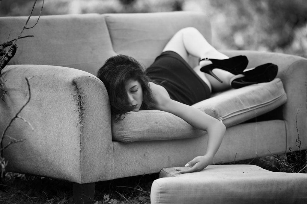 Nainen makaa sohvalla